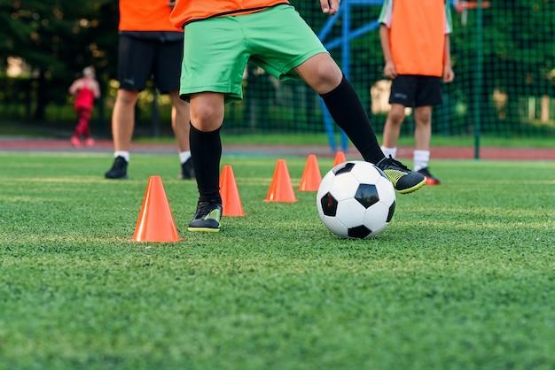 10代の少年は、サッカースタジアムのトレーニングコーンの間でボールを一周することを学びます。