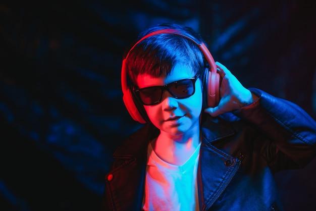 ヘッドフォンで音楽を聴いている10代の少年、ネオンライトトレンドの肖像画。カメラを見る