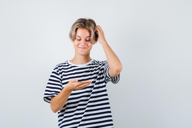 10대 소년이 손바닥을 보고 티셔츠를 입고 머리를 긁적이며 유쾌하게 보고 있습니다. 전면보기.
