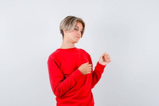 赤いセーターで目をそらし、夢中になっている、正面図を見て10代の少年。