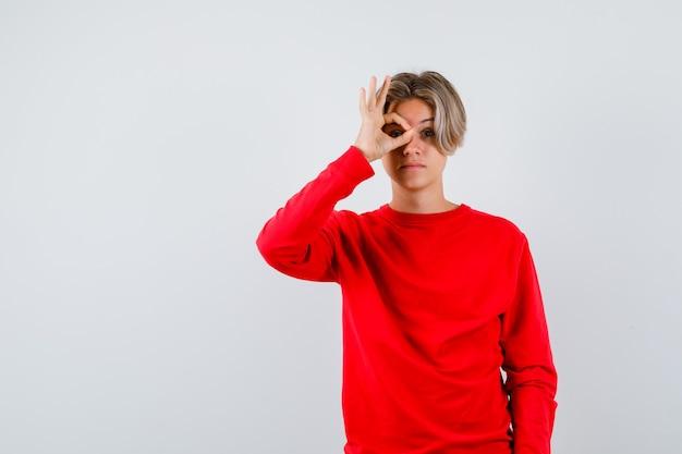 Мальчик-подросток просматривает пальцы в красном свитере и смотрит сосредоточенным. передний план.