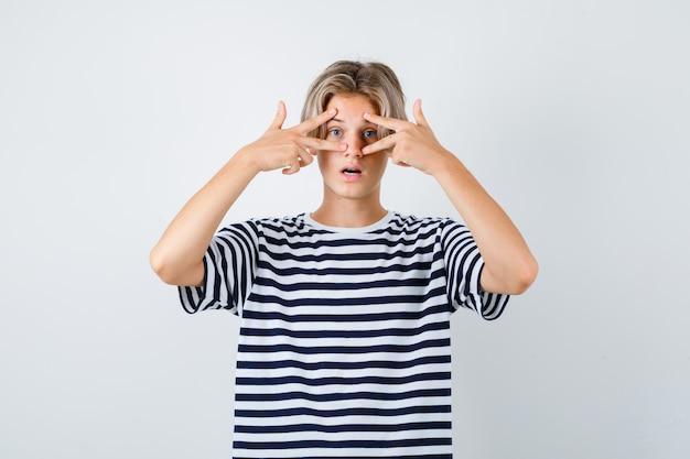 Ragazzo teenager che guarda attraverso le dita in maglietta e sembra scioccato, vista frontale.