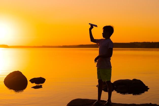 십 대 소년 오렌지 일몰에 손에 종이 비행기를 살펴봅니다. 물에 대 한 종이 접기 비행기와 아이의 실루엣. 여름 직업.