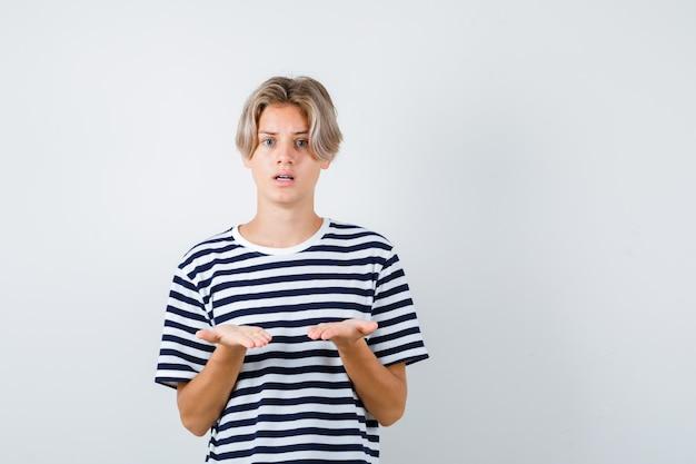 Tシャツで質問ジェスチャーをして困惑している10代の少年。正面図。