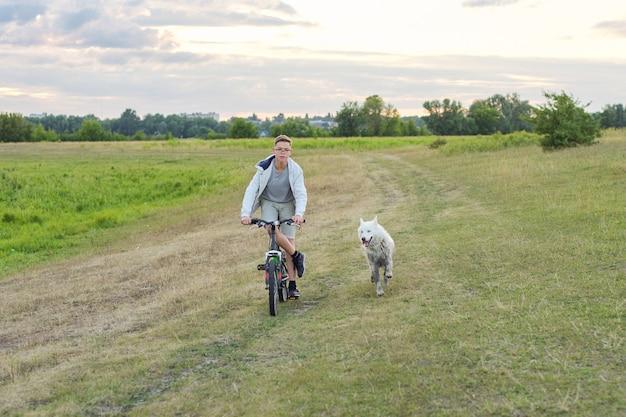 走っている犬と自転車で10代の少年、子供とペットの友情、自然の風景の牧草地