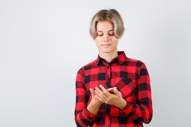 Teen boy in plaid shirt looking at her palms and looking thoughtful , front view.