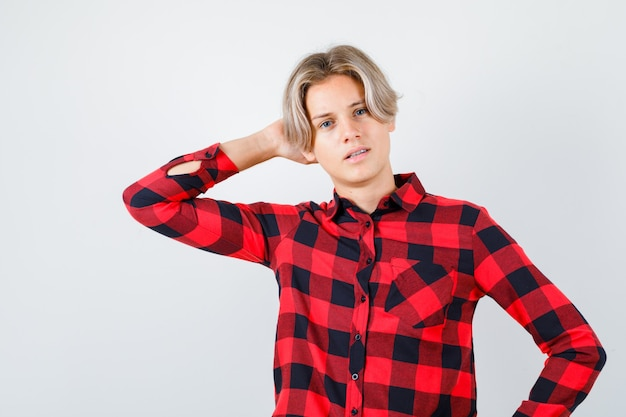 Teen boy in plaid shirt with hand behind head and looking wistful , front view.