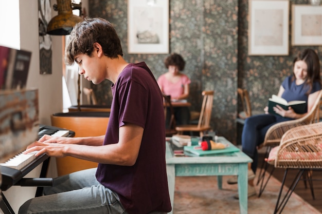 Teen boy playing piano in cafe