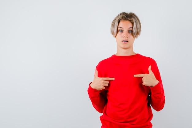 赤いセーターを着て自分を指差してショックを受けた10代の少年。正面図。