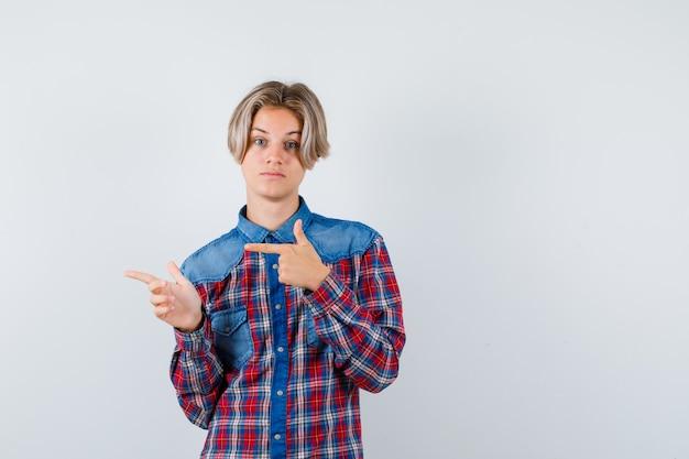 市松模様のシャツを着て左側を指して、焦点を合わせているように見える10代の少年。正面図。