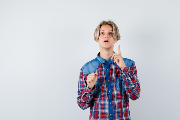 Teen boy pointing up in checkered shirt and looking perplexed. front view.