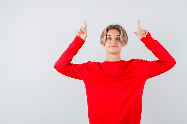 10대 소년이 빨간 스웨터를 입고 기뻐하며 정면을 바라보고 있습니다.
