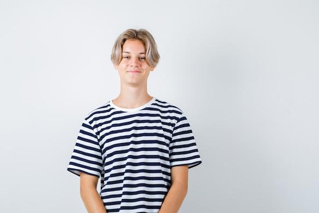 Tシャツに立って喜んで見ながらポーズをとる10代の少年。正面図。