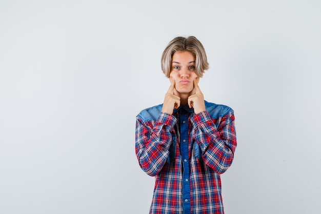 市松模様のシャツの頬に指を押して、がっかりしているように見える十代の少年。正面図。