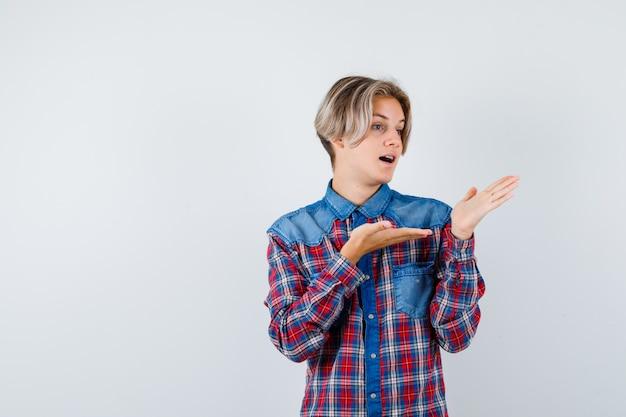 Ragazzo adolescente che finge di mostrare qualcosa in camicia a scacchi e sembra perplesso, vista frontale.
