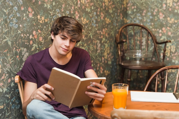 Teen boy reading at cafe table