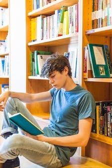 Подросток читает в тихой библиотеке