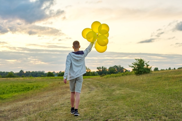 Teen boy running with balloons, view back. nature, meadow, sky in clouds background. holiday, birthday, lifestyle freedom concept