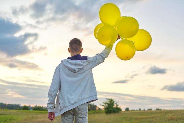 風船で走っている10代の少年、振り返ってください。自然、牧草地、雲の背景の空。休日、誕生日、ライフスタイルの自由の概念