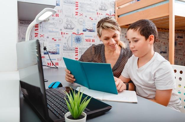 10代の少年の学校の生徒は家からノートを作ってオンラインで勉強しています。 10代の学生が宿題をしているラップトップでビデオ学習を聞いて遠隔学習。