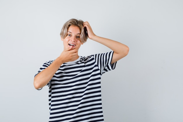 10대 소년이 티셔츠를 입은 턱에 손을 대고 놀라면서 머리를 긁적입니다. 전면보기.