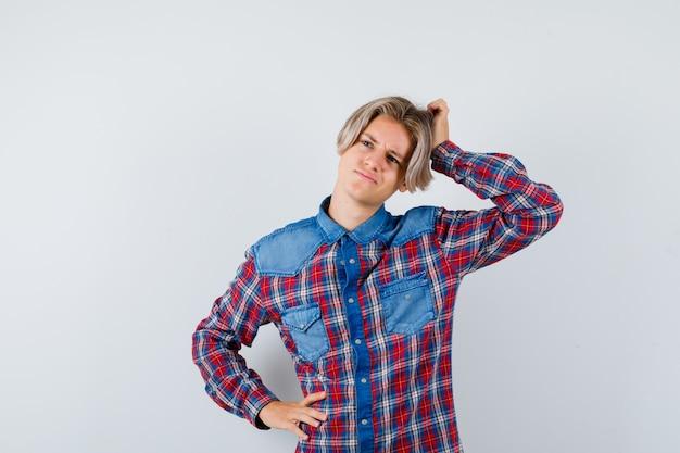 市松模様のシャツを脇に見ながら、思慮深く見ながら頭を掻く10代の少年。正面図。