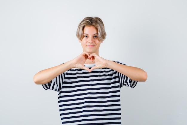 10대 소년이 티셔츠에 하트 제스처를 보이고 친절하게 보입니다. 전면보기.