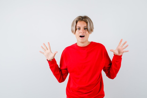 항복 제스처에 손바닥을 보여주는 십 대 소년, 빨간 스웨터에 입을 벌리고 겁에 질린 찾고. 전면보기.