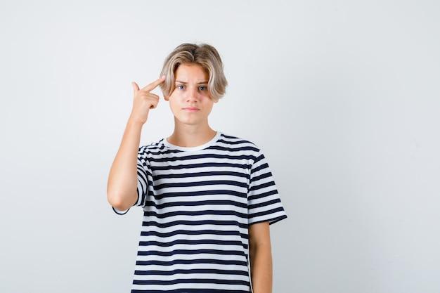 Tシャツで自殺ジェスチャーを示し、イライラしているように見える10代の少年。正面図。