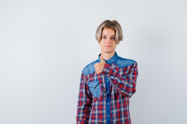 市松模様のシャツに親指を表示し、満足しているように見える10代の少年、正面図。