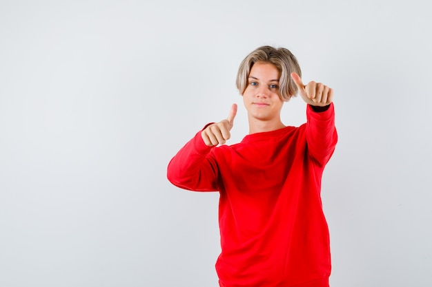 Подросток мальчик показывает палец вверх в красном свитере и выглядит довольным. передний план.