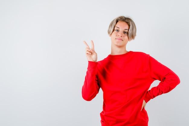 赤いセーターで勝利のジェスチャーを示し、満足しているように見える十代の少年、正面図。