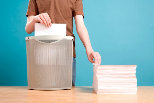 Teen boy shredding stack of paper