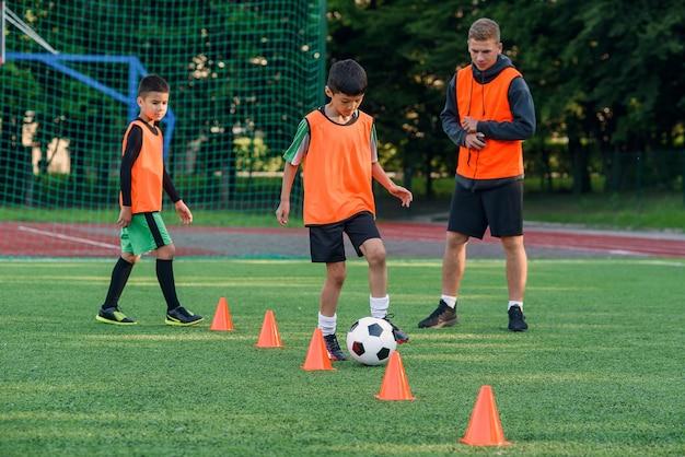 Teen boy in sportswear trains football on soccer field.