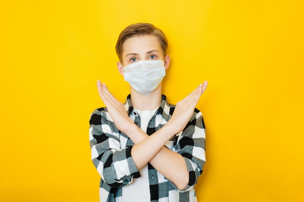 Teen boy in sterile face mask posing isolated on yellow background