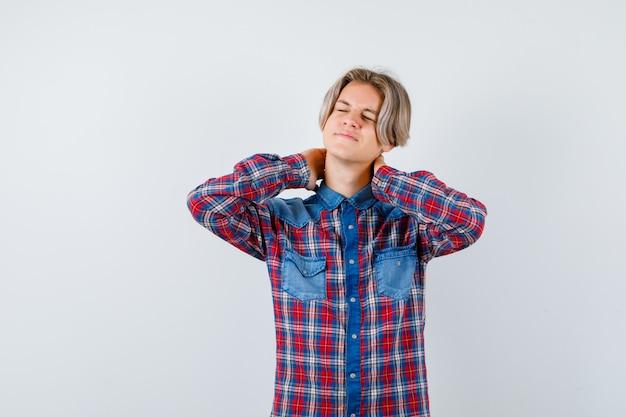 市松模様のシャツの首の痛みに苦しんでいて、痛みを伴うように見える十代の少年。正面図。