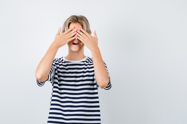 Ragazzo teenager in maglietta che copre gli occhi con le mani, aprendo la bocca e guardando eccitato, vista frontale.