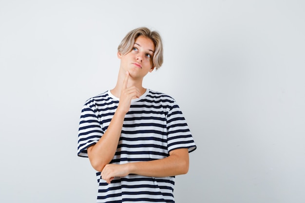 Teen boy in t-shirt keeping finger on chin and looking pensive , front view.