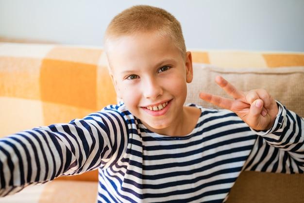 Мальчик-подросток делает селфи и любит вести блог в социальных сетях в гостиной, сидя на диване у себя дома