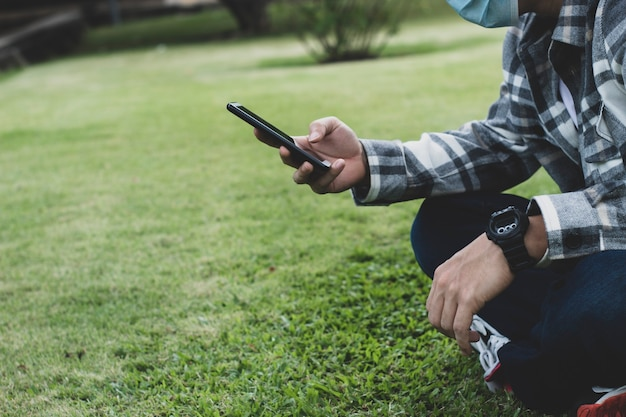 Teen boy using smartphone device for online network technology internet;  man use mobile in public park