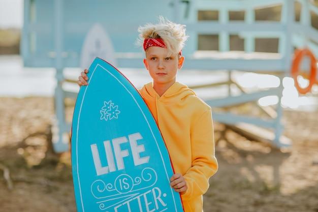 ライフガードタワーのそばに青いサーフボードを保持している赤いヘッドバンドを身に着けている10代の少年