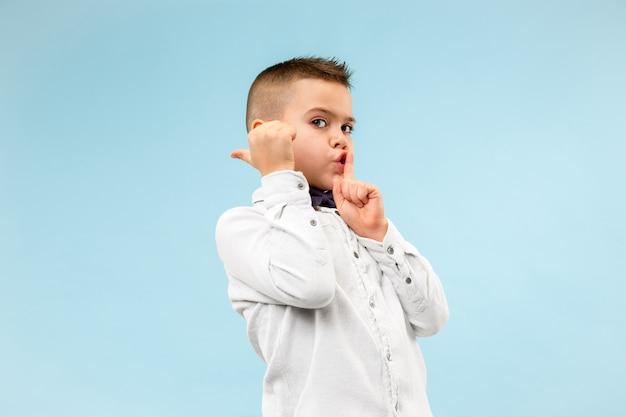 Il ragazzo adolescente che bisbiglia un segreto dietro la sua mano su sfondo blu