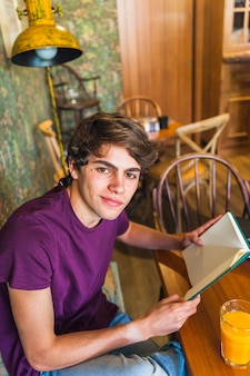 Teen boy with book looking at camera in cafe