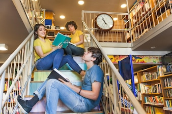 Teen boy with book looking up near friends