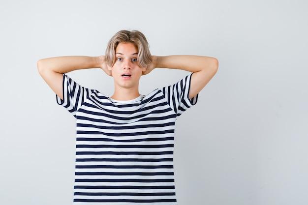 頭の後ろに手を持ち、tシャツで口を開けて驚いたように見える10代の少年。正面図。