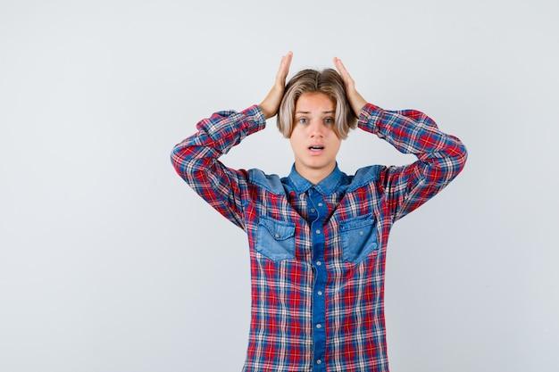 Ragazzo teenager con le mani sulla testa in camicia a scacchi e guardando smemorato, vista frontale.