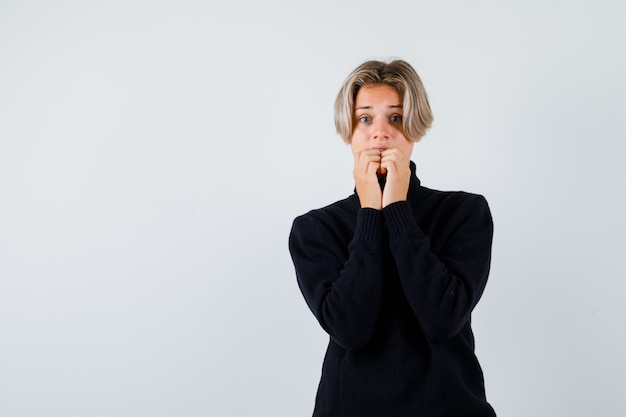 Teen boy with hands on mouth in black sweater and looking scared , front view.