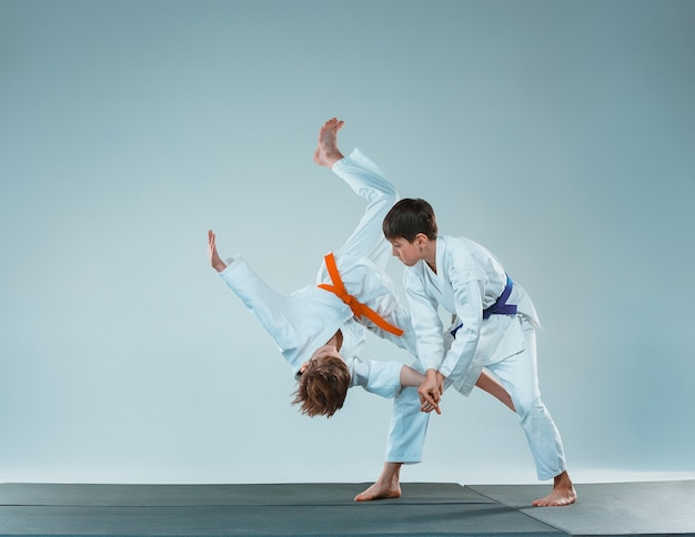 The teen boys fighting at aikido training in martial arts school. healthy lifestyle and sports concept. teenagers in white kimono on white background. children with concentrated faces
