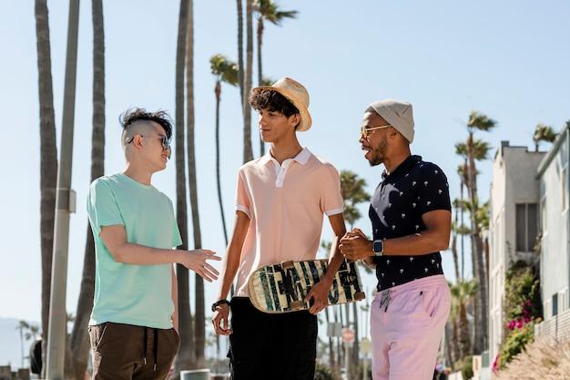 ぶらぶらしている10代の少年、ロサンゼルスのベニスビーチで夏の日
