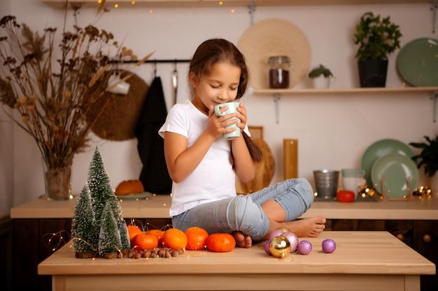 Teen brunette girl drinking tea in christmas kitchen